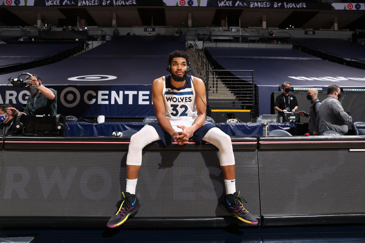 Karl-Anthony Towns sitting on the sideline with a headset on