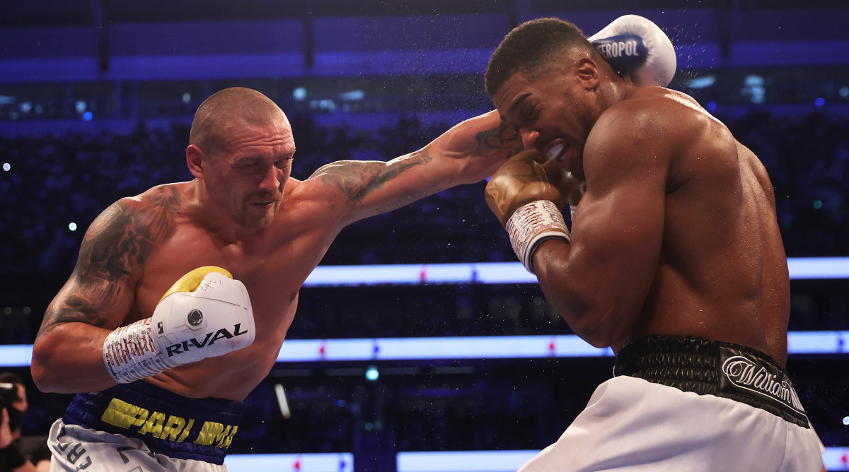 Oleksandr Usyk punches as Anthony Joshua ducks during the Heavyweight Title Fight between Anthony Joshua and Oleksandr Usyk at Tottenham Hotspur Stadium on September 25, 2021 in London, England.