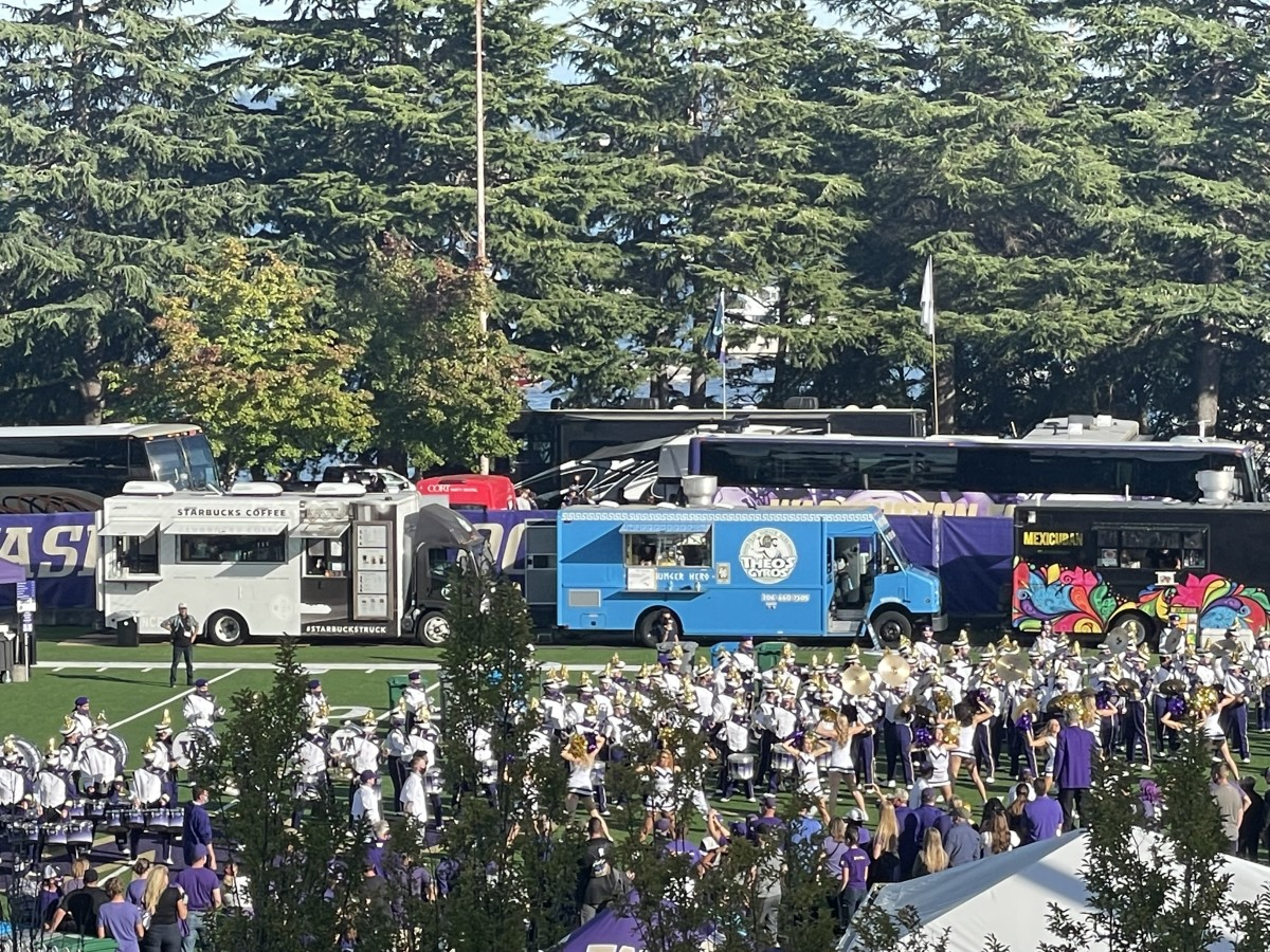 Husky busses arrive while fans, cheerleaders and band members await them.
