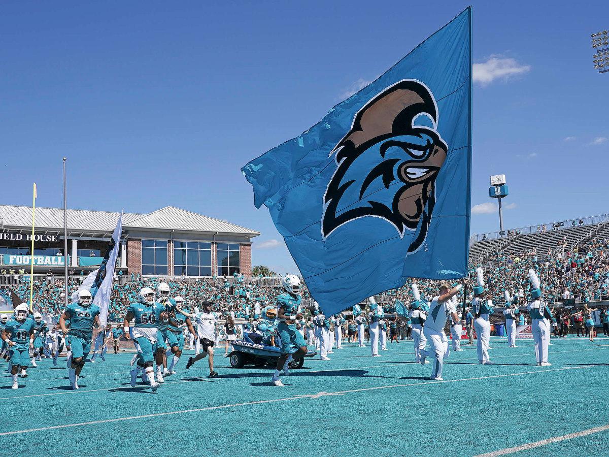 Coastal Carolina carries a school flag onto the field