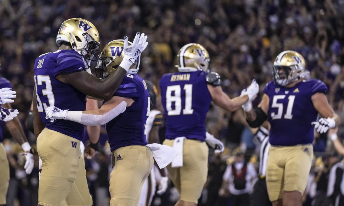 Tight end Devin Culp congratulates Sean McGrew after his touchdown run.