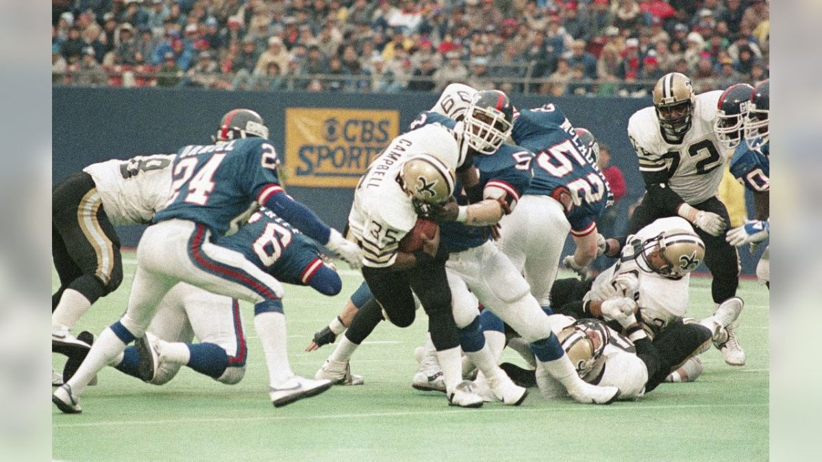 Former New Orleans Saints RB Earl Campbell (35) is stopped by Giants LB Lawrence Taylor during a 1985 game. Credit: Giants.com