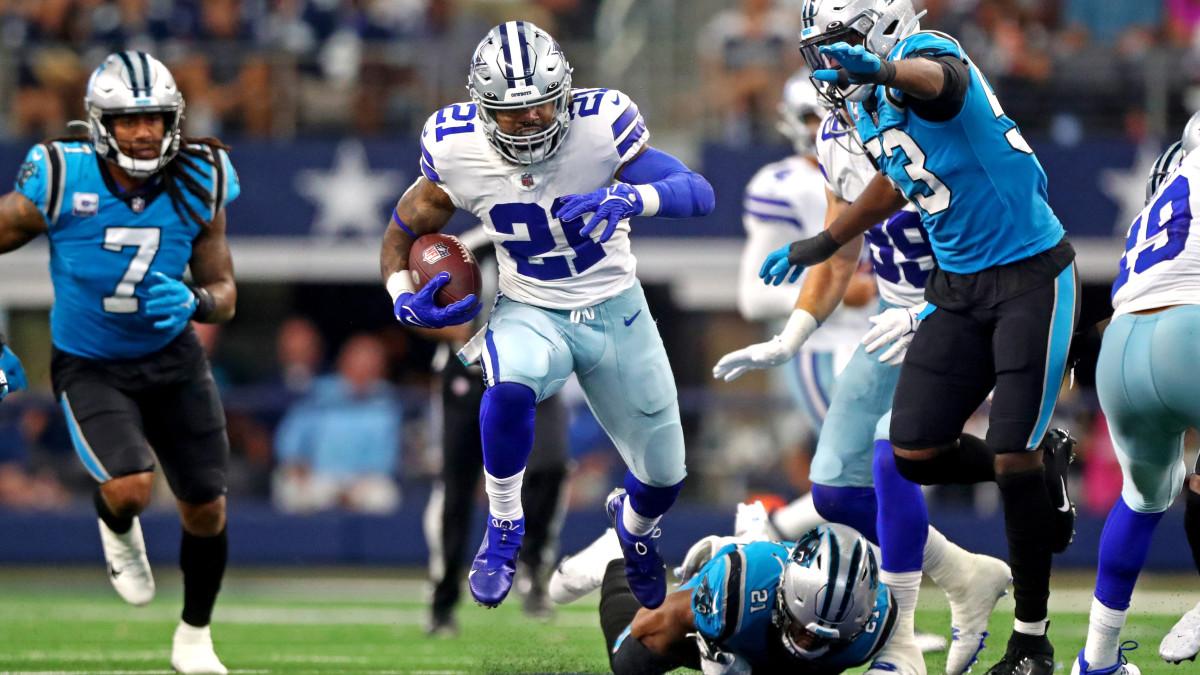 Dallas Cowboys running back Ezekiel Elliott (21) runs the ball against Carolina Panthers defensive end Brian Burns (53) during the second half at AT&T Stadium.