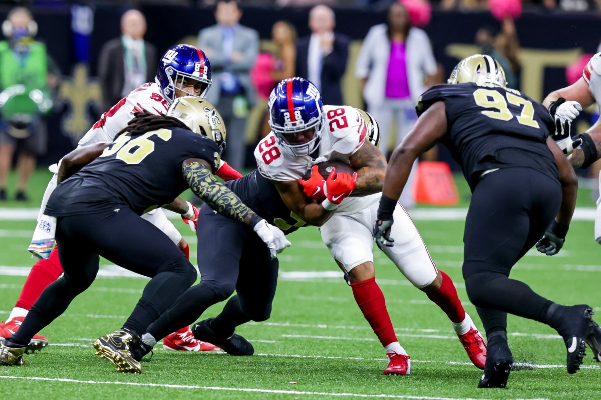 Giants running back Devontae Booker (28) rushes into New Orleans Saints linebacker Demario Davis (56) and defensive tackle Malcolm Roach (97). Mandatory Credit: Stephen Lew-USA TODAY Sports