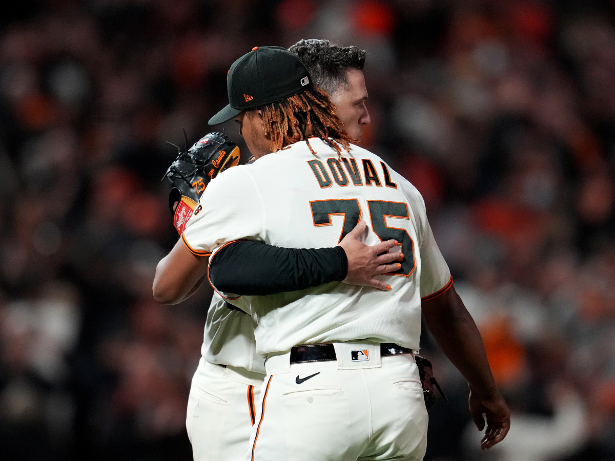 Oct 8, 2021; San Francisco, California, USA; San Francisco Giants catcher Buster Posey (28) hugs relief pitcher Camilo Doval (75) after defeating the Los Angeles Dodgers in game one of the 2021 NLDS at Oracle Park.