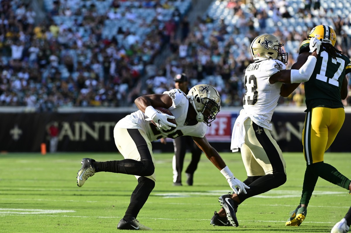 New Orleans Saints cornerback Paulson Adebo (29) returns a interception during the second half as Marshon Lattimore (23) blocks Packers receiver Davante Adams (17). Mandatory Credit: Tommy Gilligan-USA TODAY Sports