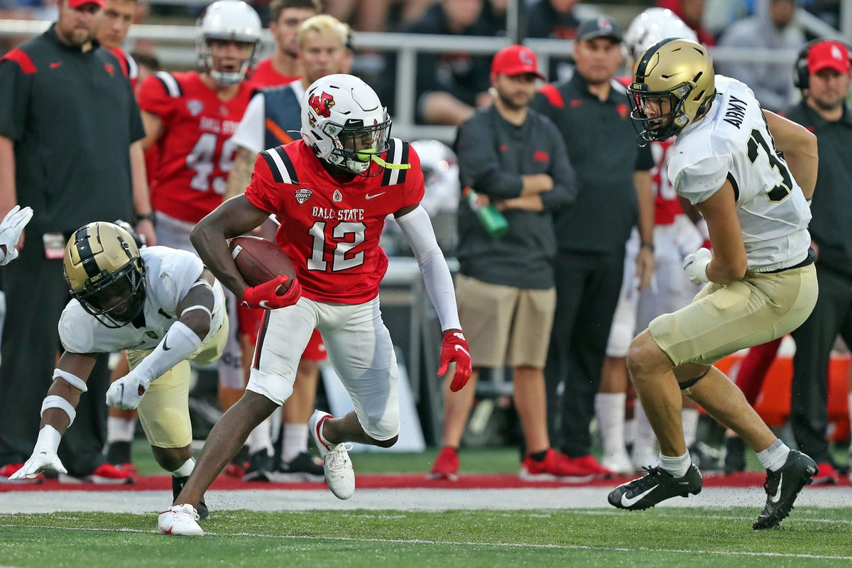 Oct 2, 2021; Muncie, Indiana, USA; Ball State Cardinals wide receiver Jayshon Jackson (12) runs after making a catch while Army Black Knights outside linebacker Andre Carter (34) defends during the second half at Scheumann Stadium. Mandatory Credit: Danny Wild-USA TODAY Sports