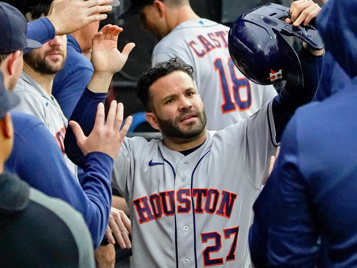 Houston Astros second baseman Jose Altuve (27) is congratulated in the dugout after scoring against the Chicago White Sox on a one-run RBI single hit by left fielder Michael Brantle