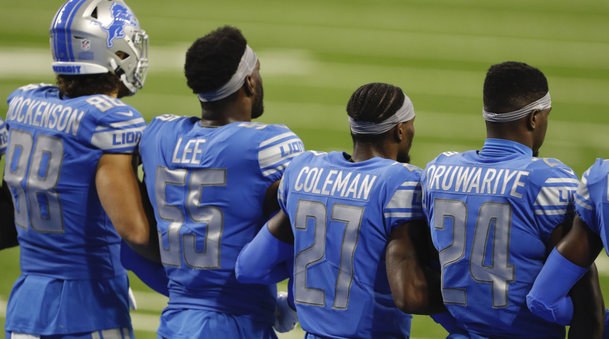 Detroit Lions players stand arm in arm