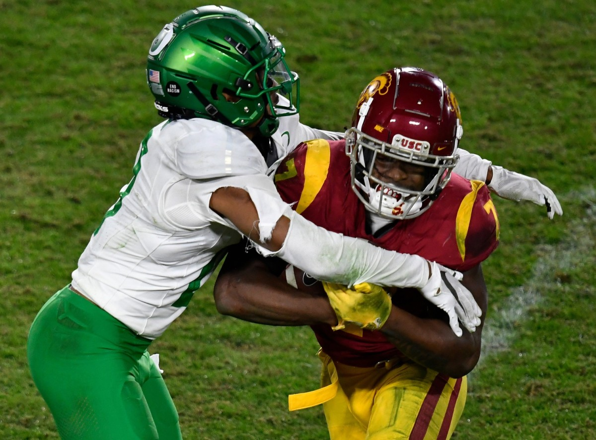 Oregon Ducks cornerback Deommodore Lenoir (0) tackles USC Trojans running back Stephen Carr (7) during the fourth quarter at United Airlines Field at Los Angeles Memorial Coliseum.