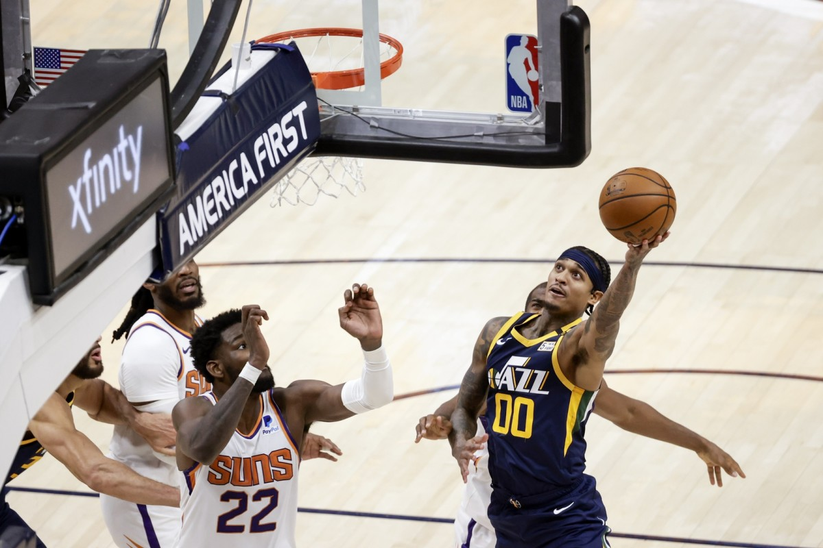 Jordan Clarkson (00) shoots a layup over DeAndre Ayton (22) and the Phoenix Suns