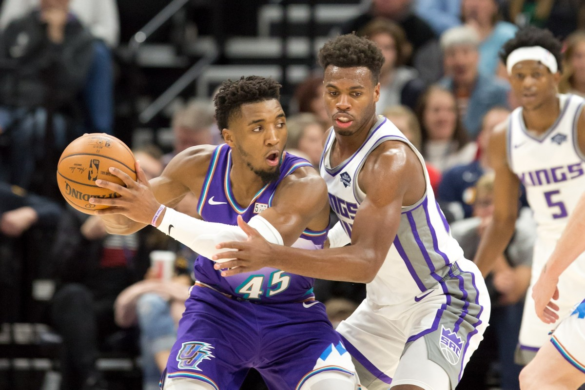 Donovan Mitchell (45) survey's the floor against Buddy Hield (24) as De'Aaron Fox (5) lurks in the background