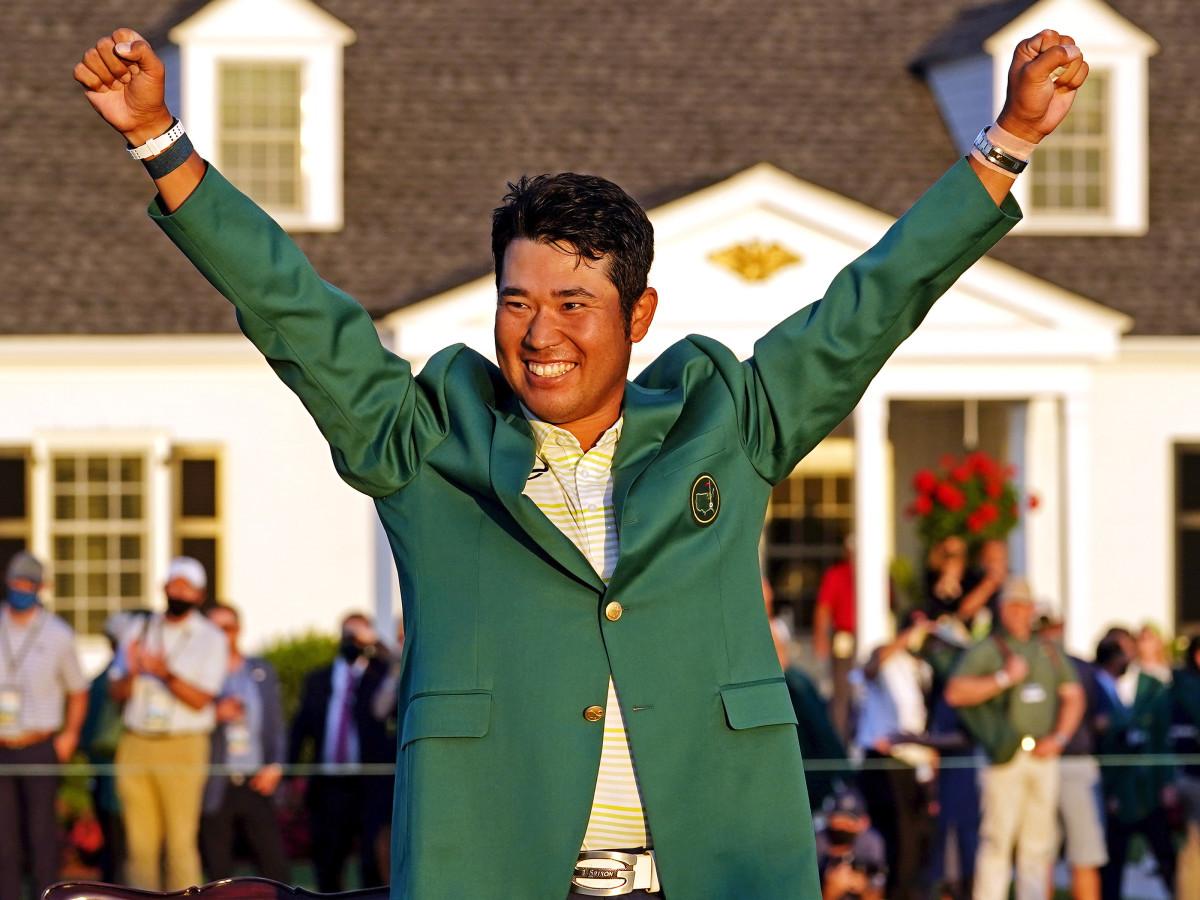Hideki Matsuyama celebrates with the green jacket after winning The Masters golf tournament.