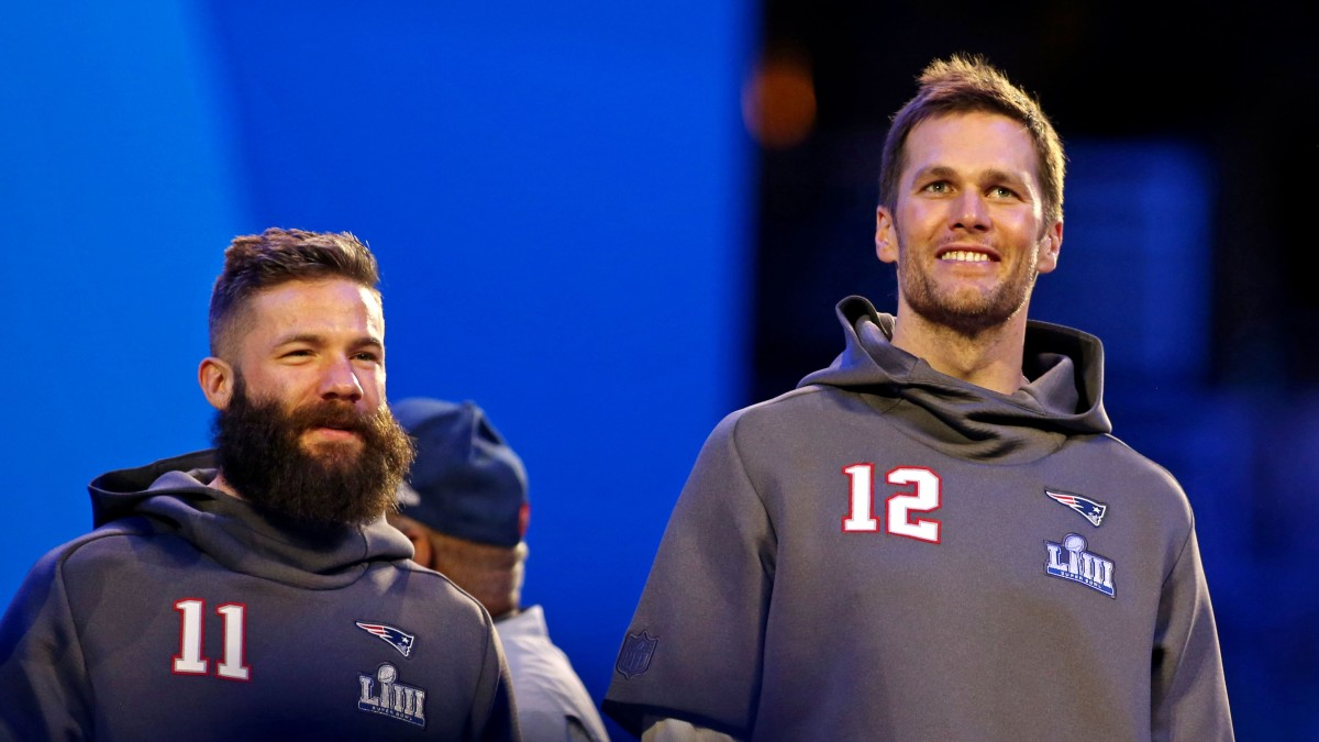 Julian Edelman and Tom Brady look on during Super Bowl media day