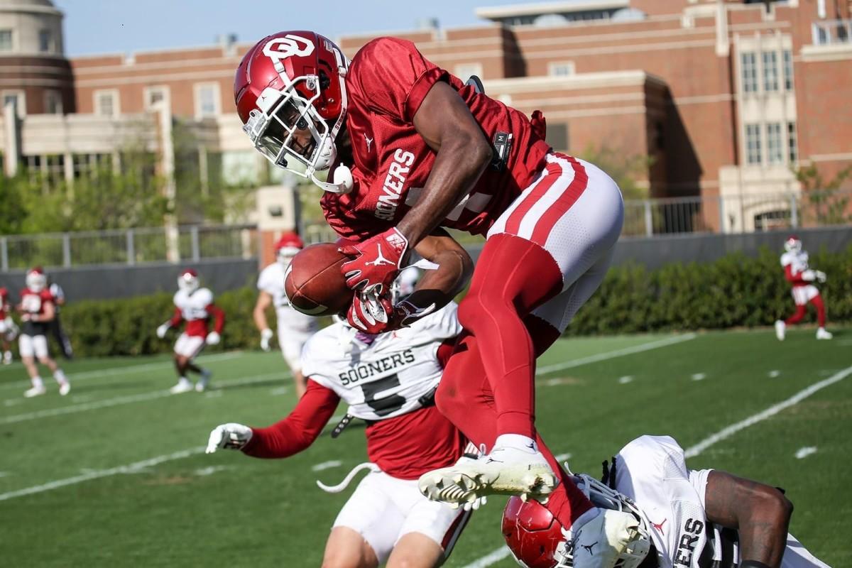 Mario Williams elevates between two Sooner defenders at practice