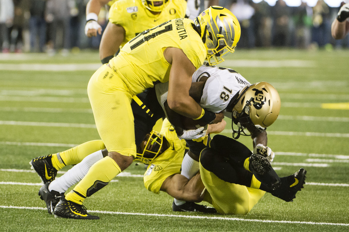 Isaac Slade-Matautia tackles wide receiver Tony Brown in a game against the Colorado Buffaloes at Autzen Stadium.