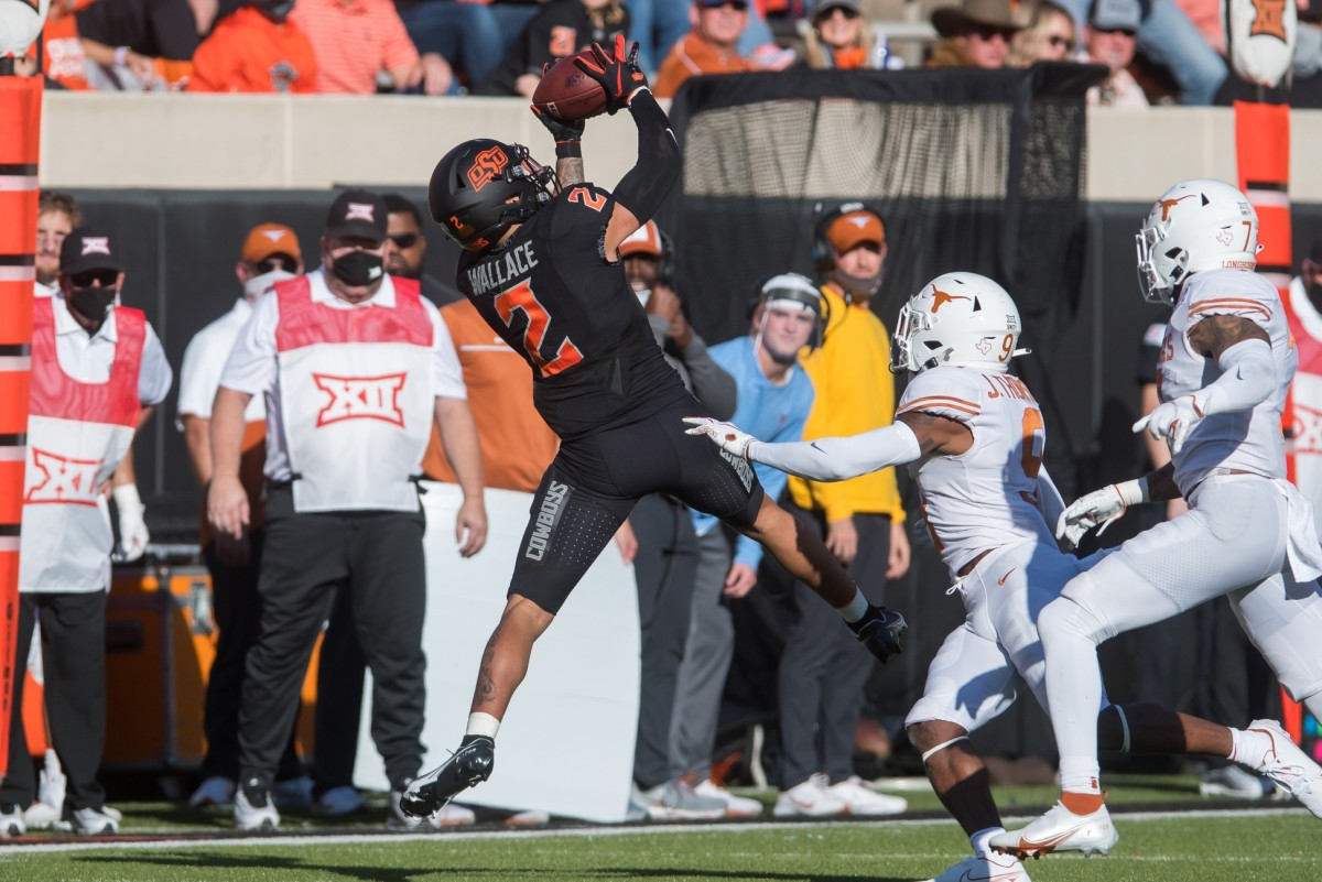 Oklahoma State receiver Tylan Wallace (2) makes a reception against Texas defensive backs Josh Thompson (9) and Caden Sterns (7). Mandatory Credit: Brett Rojo-USA TODAY