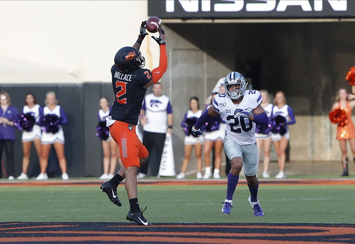 Oklahoma State Cowboys receiver Tylan Wallace (2) makes a catch ahead of Kansas State defensive back Denzel Goolsby (20). Mandatory Credit: Alonzo Adams-USA TODAY