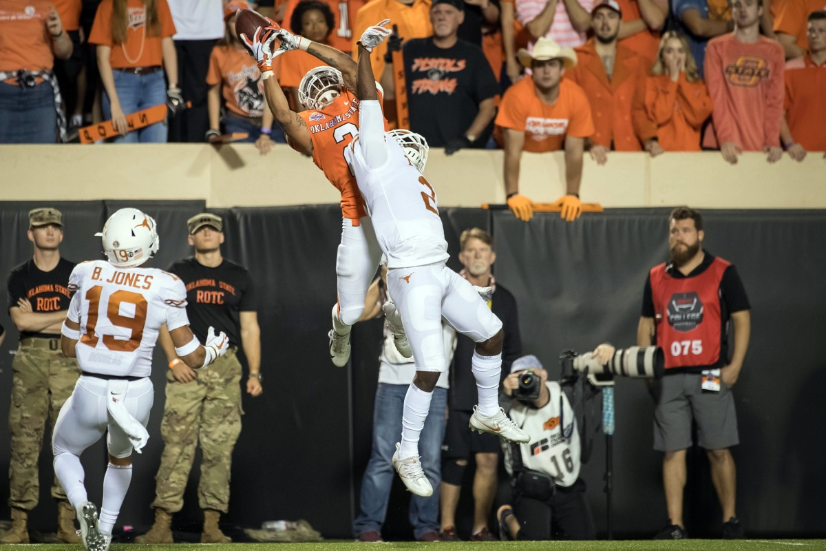 Oklahoma State Cowboys wide receiver Tylan Wallace (2) makes a catch while defended by Texas defensive back Brandon Jones (19). Mandatory Credit: Rob Ferguson-USA TODAY