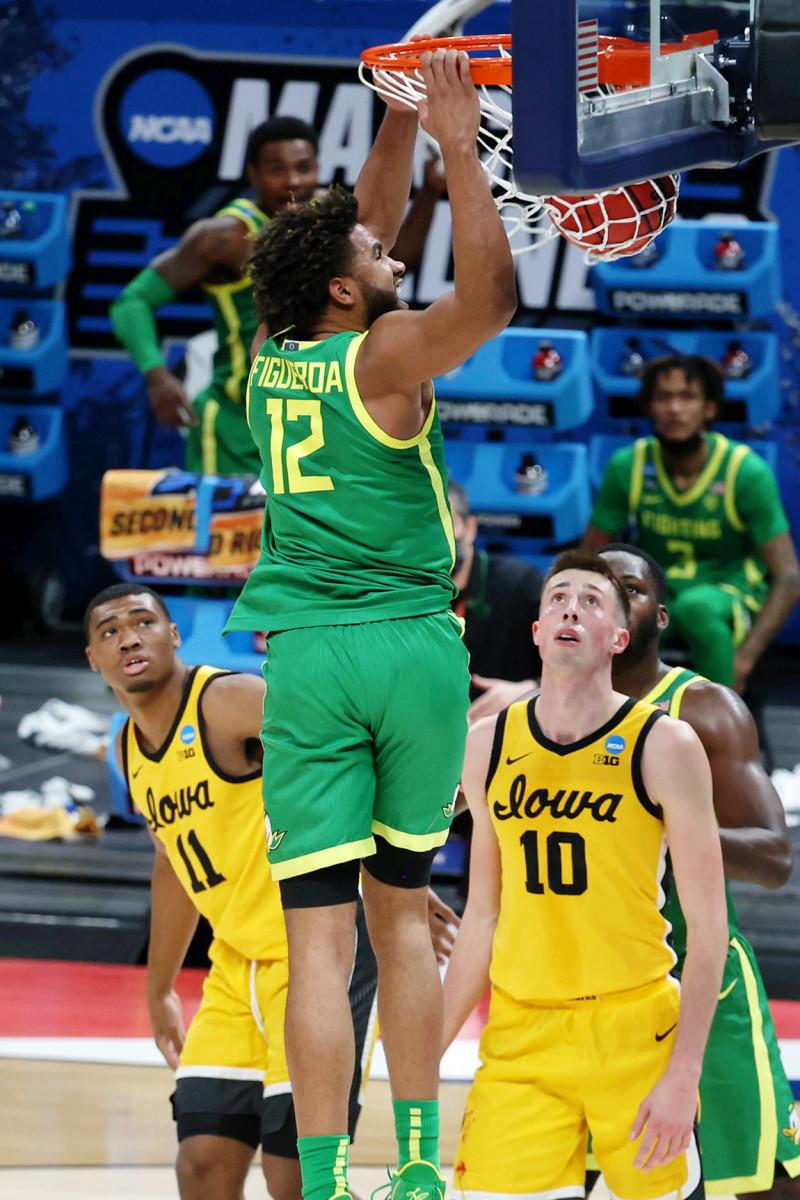 LJ Figueroa (12) throws down a dunk in the NCAA Tournament while Iowa's Joe Wieskamp (10) and Tony Perkins (11) look on.