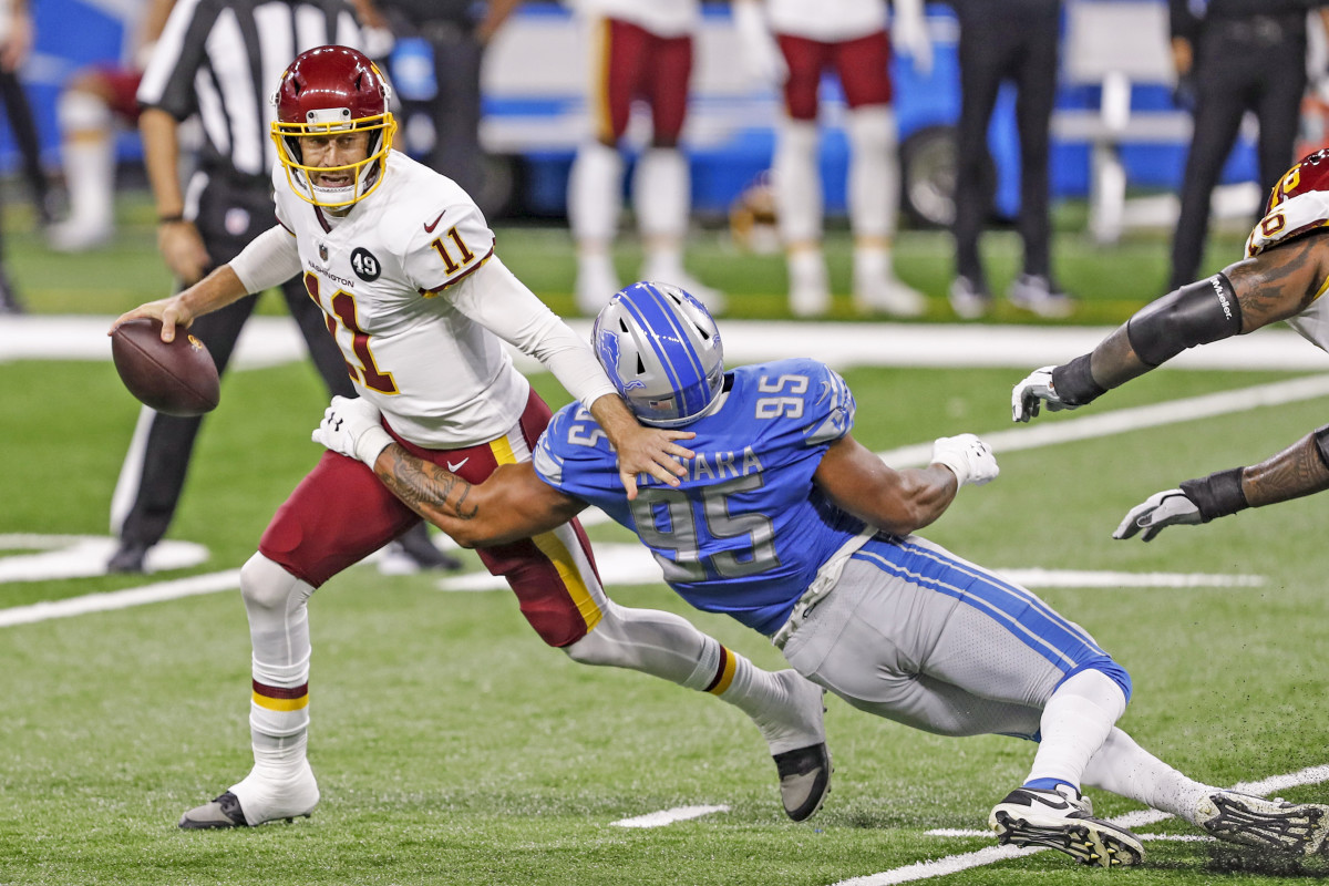 Alex Smith avoids a sack during a 2020 game against the Lions, his first start since his injury