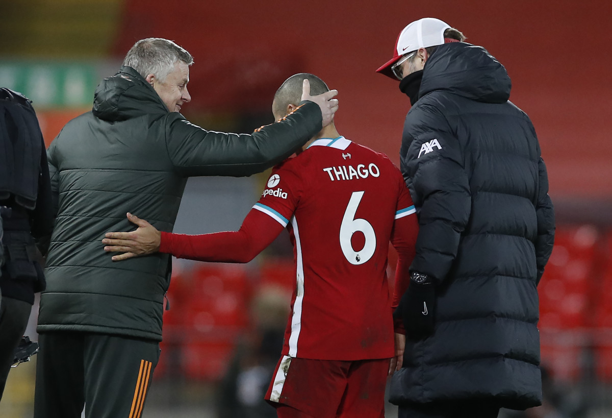 Thiago Alcantara between Manchester United's Ole Gunnar Solskjaer and Liverpool's Jurgen Klopp.