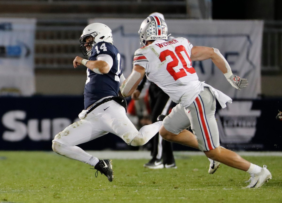 Penn State quarterback Sean Clifford (14) slides in front of Ohio State linebacker Pete Werner (20)Adam Cairns/Columbus Dispatch via Imagn Content Services, LLC