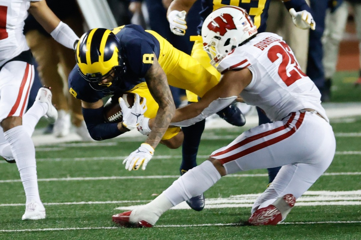 Michigan receiver Ronnie Bell (8) is tackled by Wisconsin Badgers safety Eric Burrell (25). Mandatory Credit: Rick Osentoski-USA TODAY