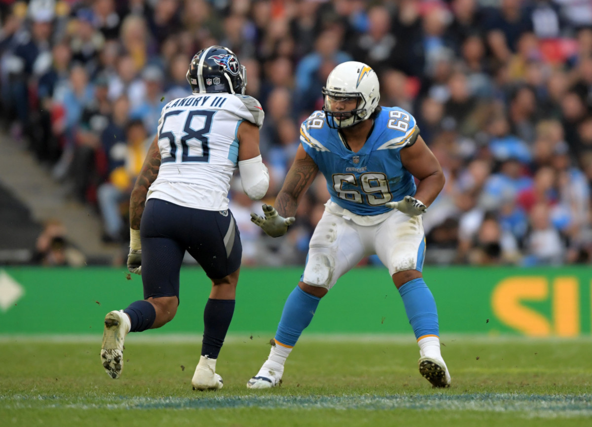 Oct 21, 2018; London, United Kingdom; Los Angeles Chargers offensive tackle Sam Tevi (69) defends against Tennessee Titans linebacker Harold Landry (58) in the second half during an NFL International Series game at Wembley Stadium. The Chargers defeated the Titans 20-19.