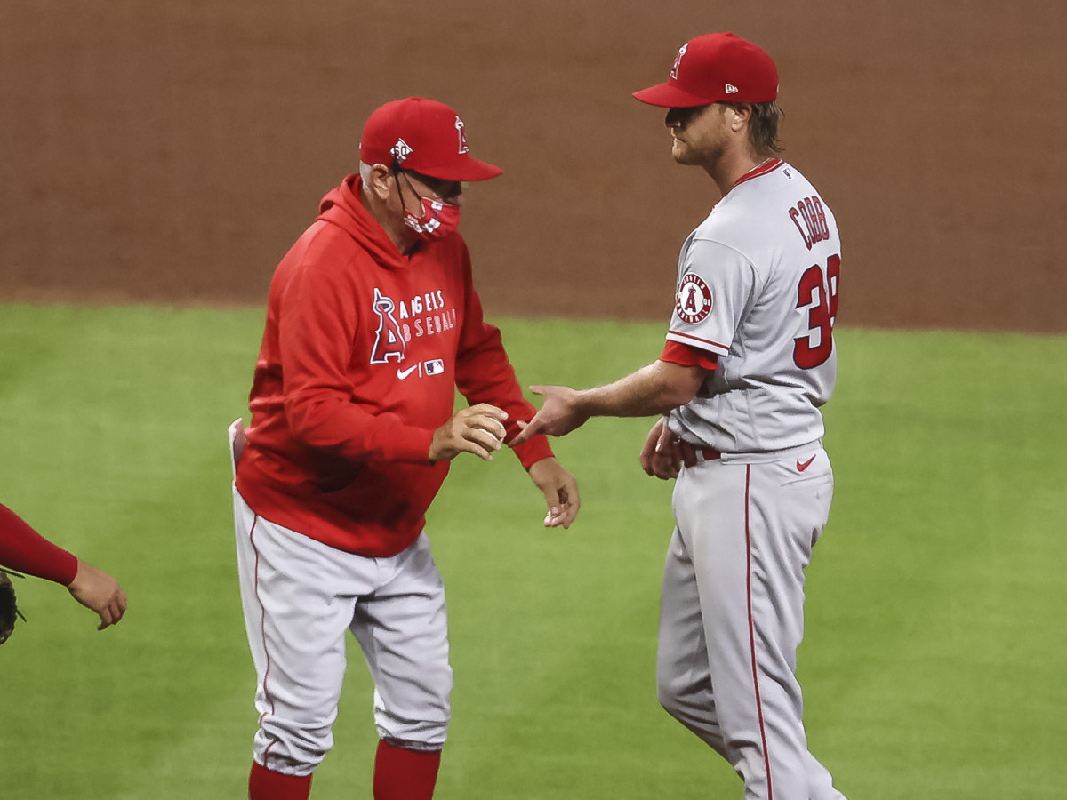 Los Angeles Angels manager Joe Maddon (right) gives the ball to relief pitcher Alex Claudio (58) in the sixth inning against the Texas Rangers at Angel Stadium.