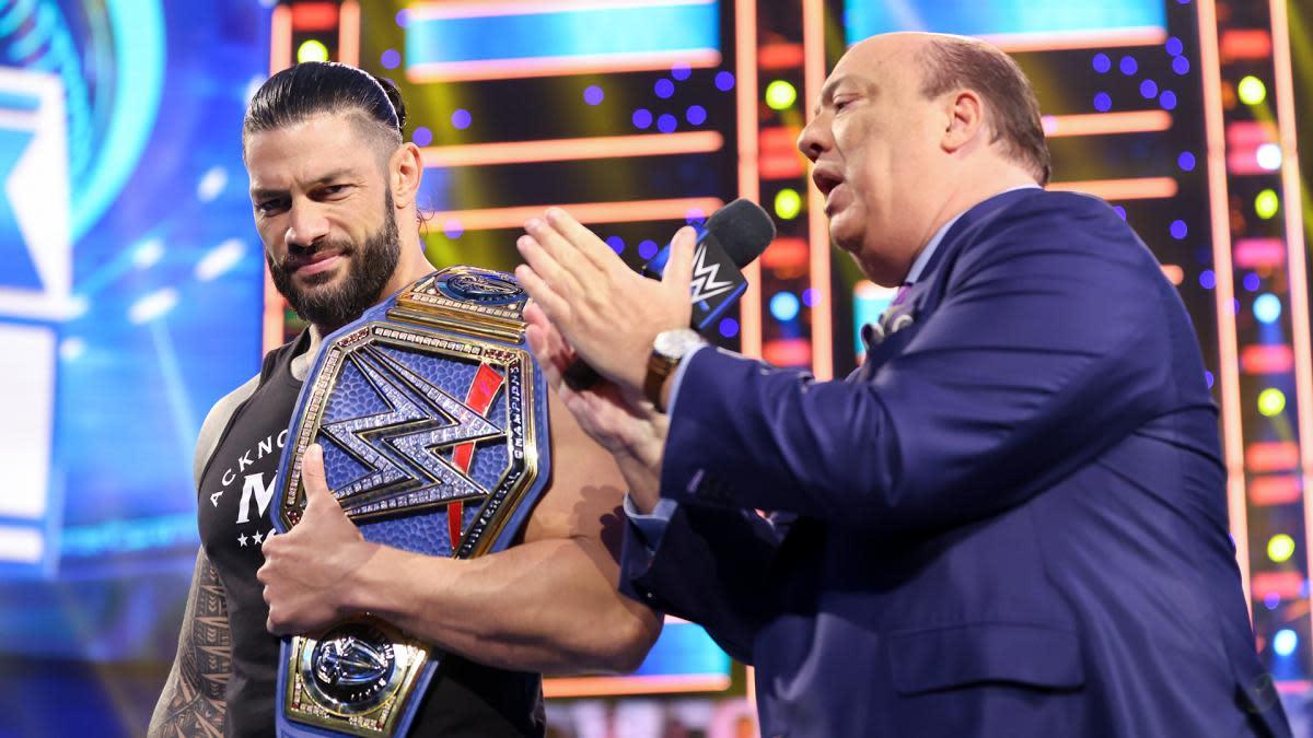 Paul Heyman on the microphone beside Roman Reigns on SmackDown