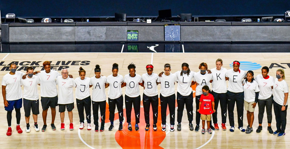 The Mystics players spelling out JACOB BLAKE on their T-shirts