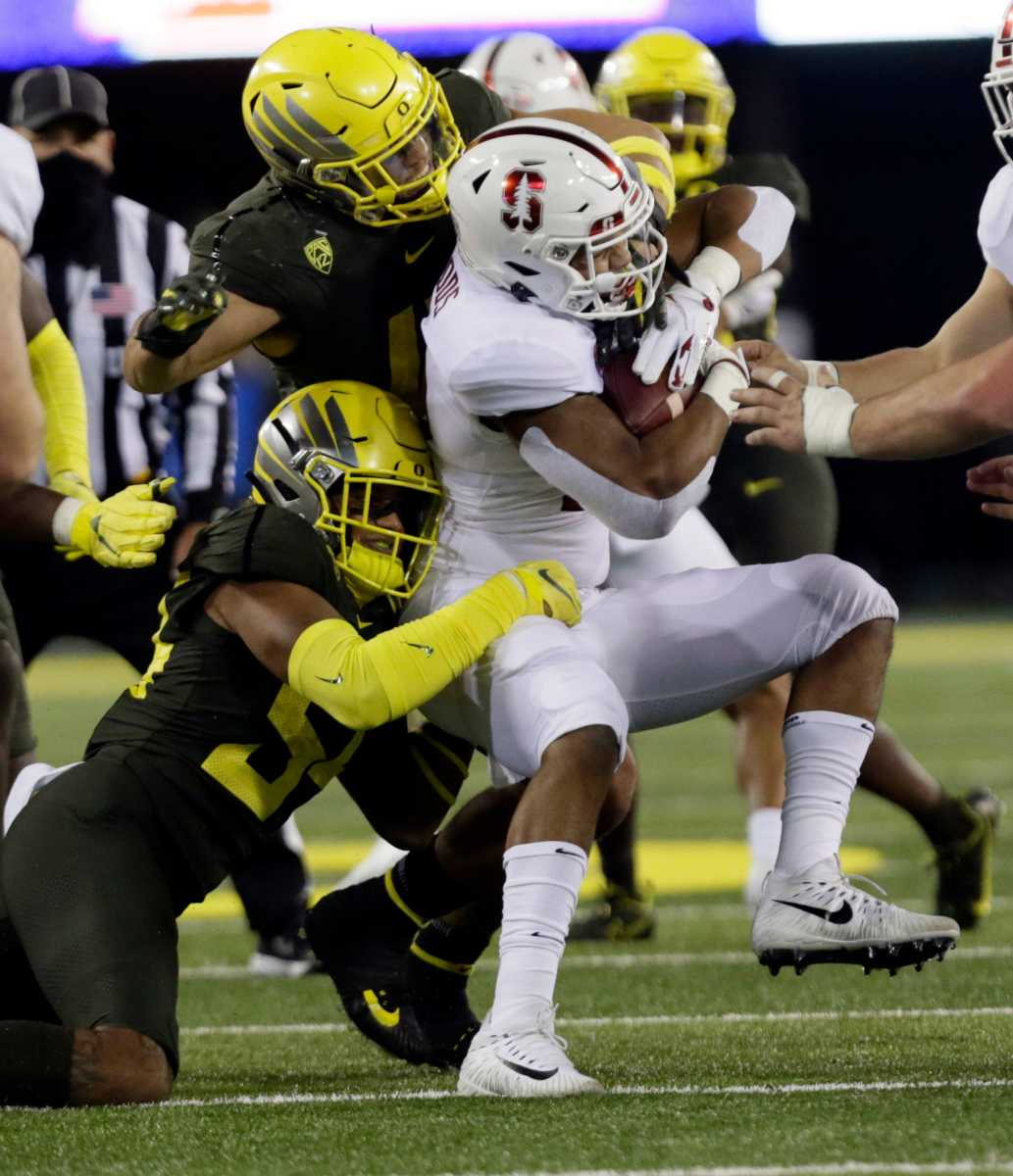 Dru Mathis (54) works with Isaac Slade-Matautia (41) to bring down Stanford running back Justus Woods.
