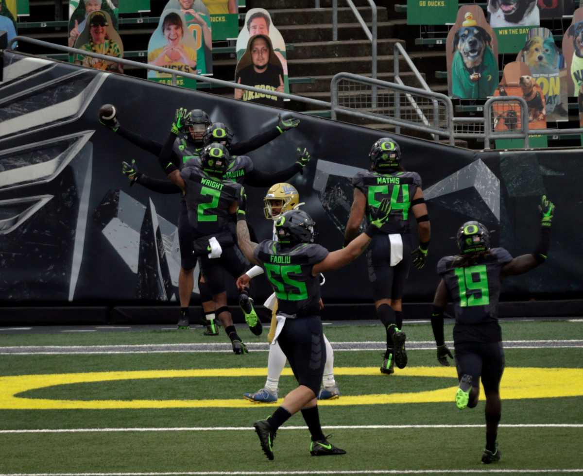Jordan Happle celebrates a pick-six with teammates as time expires against the UCLA Bruins.