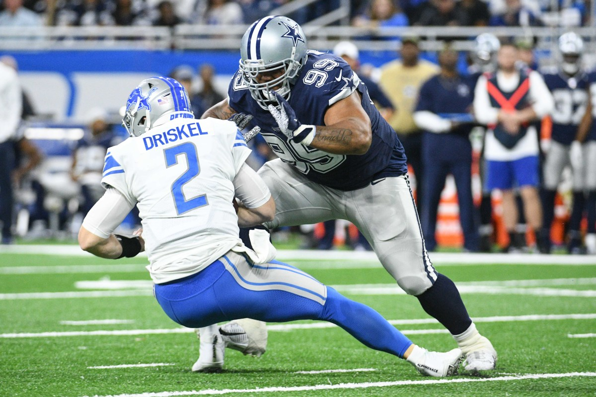 Nov 17, 2019; Detroit, MI, USA; Dallas Cowboys defensive tackle Antwaun Woods (99) tackles Detroit Lions quarterback Jeff Driskel (2) during the second half at Ford Field.