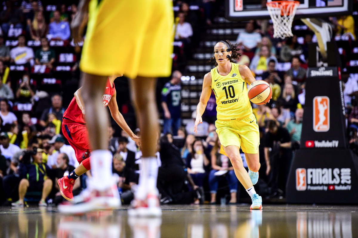 Sue Bird dribbles, wearing a nose mask
