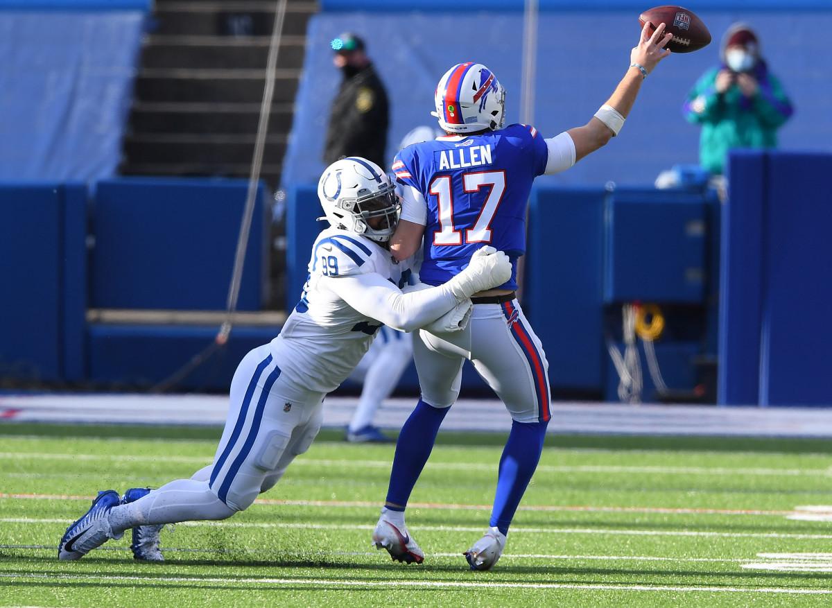 Jan 9, 2021; Orchard Park, New York, USA; Buffalo Bills quarterback Josh Allen (17) throws under pressure against Indianapolis Colts defensive tackle DeForest Buckner (99) during the first half in the AFC Wild Card game at Bills Stadium.