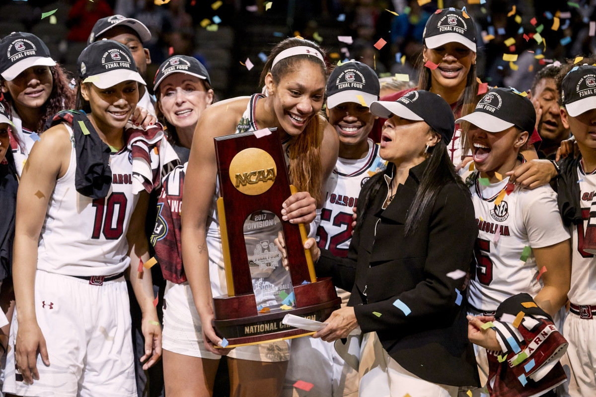 Dawn Staley holds the NCAA trophy with A'ja Wilson and her teammates
