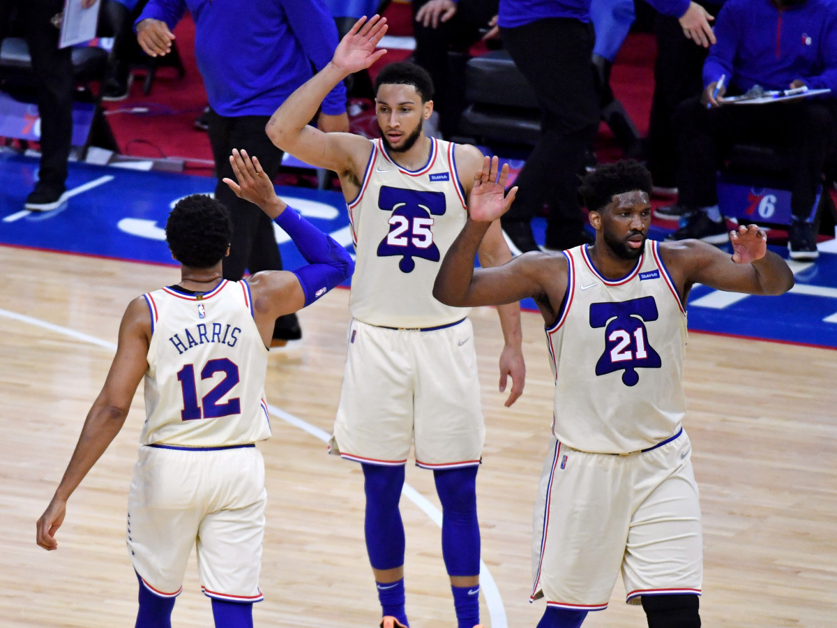 Apr 14, 2021; Philadelphia, Pennsylvania, USA; Philadelphia 76ers forward Tobias Harris (12) celebrates with guard Ben Simmons (25) and center Joel Embiid (21) against the Brooklyn Nets during the second quarter at Wells Fargo Center.