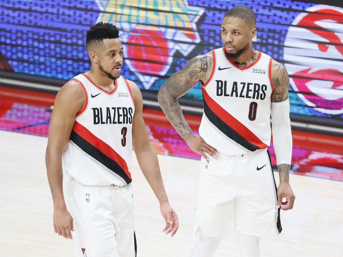 Portland Trail Blazers shooting guard CJ McCollum (3) and point guard Damian Lillard (0) walk back to the court after a timeout during the second half of game three in the first round