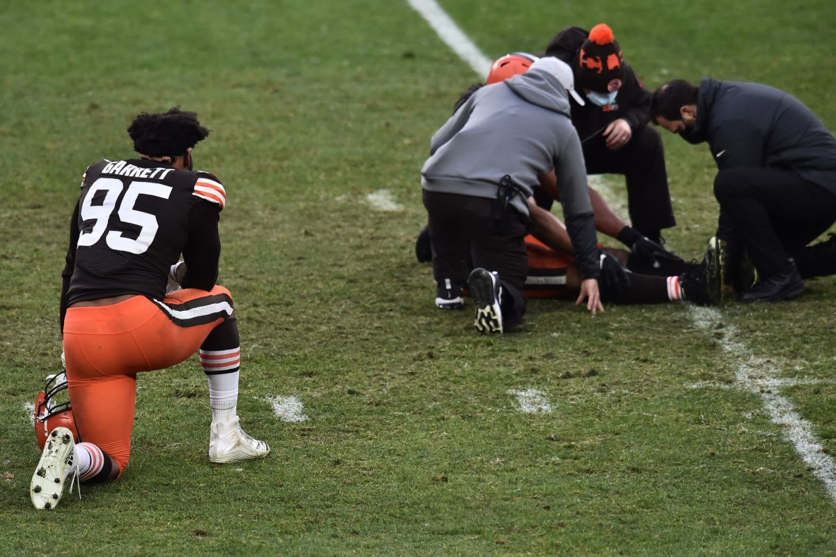 Jan 3, 2021; Cleveland, Ohio, USA; Cleveland Browns defensive end Myles Garrett (95) kneels as trainers look at defensive end Olivier Vernon (54) during the second half against the Pittsburgh Steelers at FirstEnergy Stadium. Mandatory Credit: Ken Blaze-USA TODAY Sports