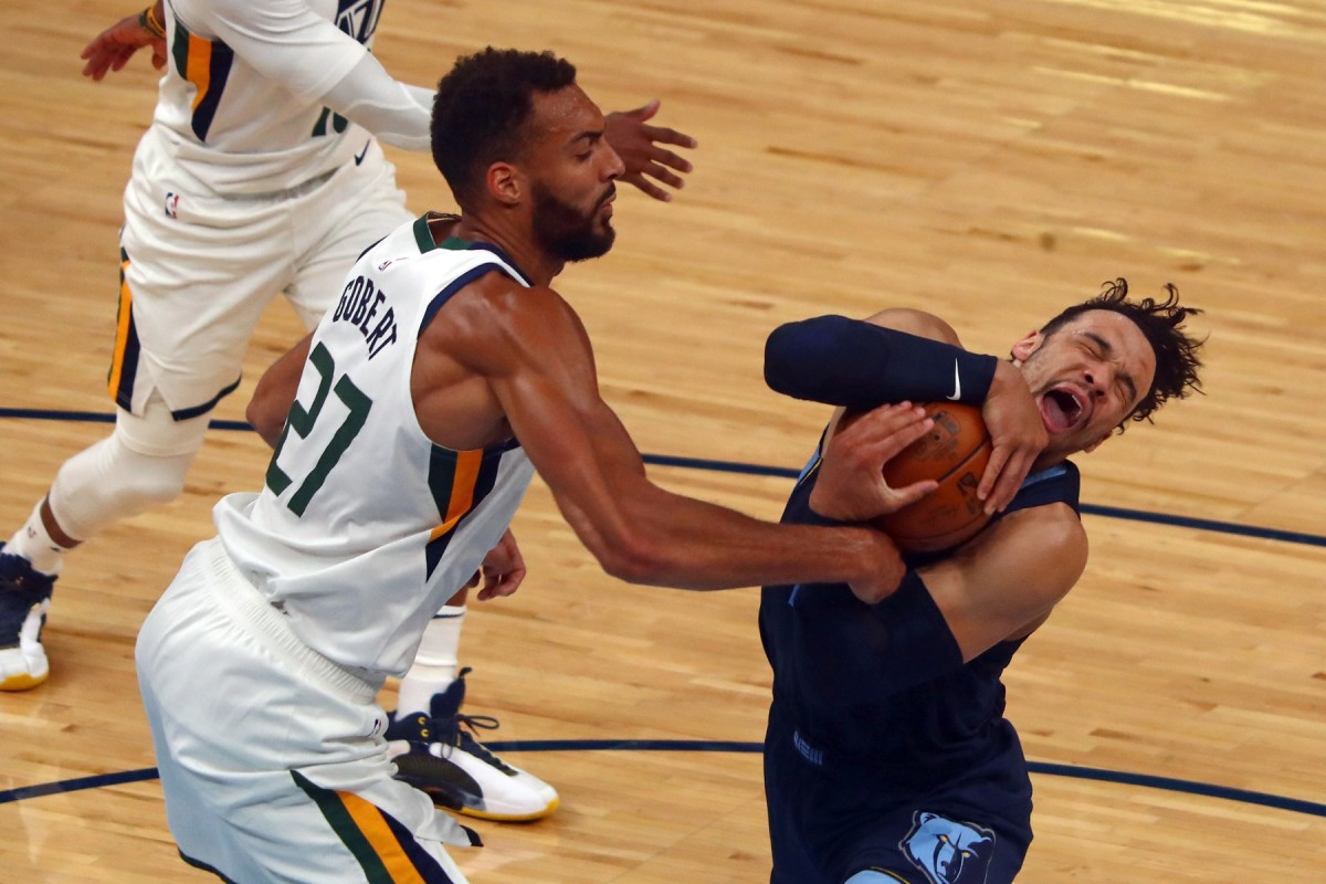 Rudy Gobert (27) tries to strip the ball from Dillon Brooks (24)