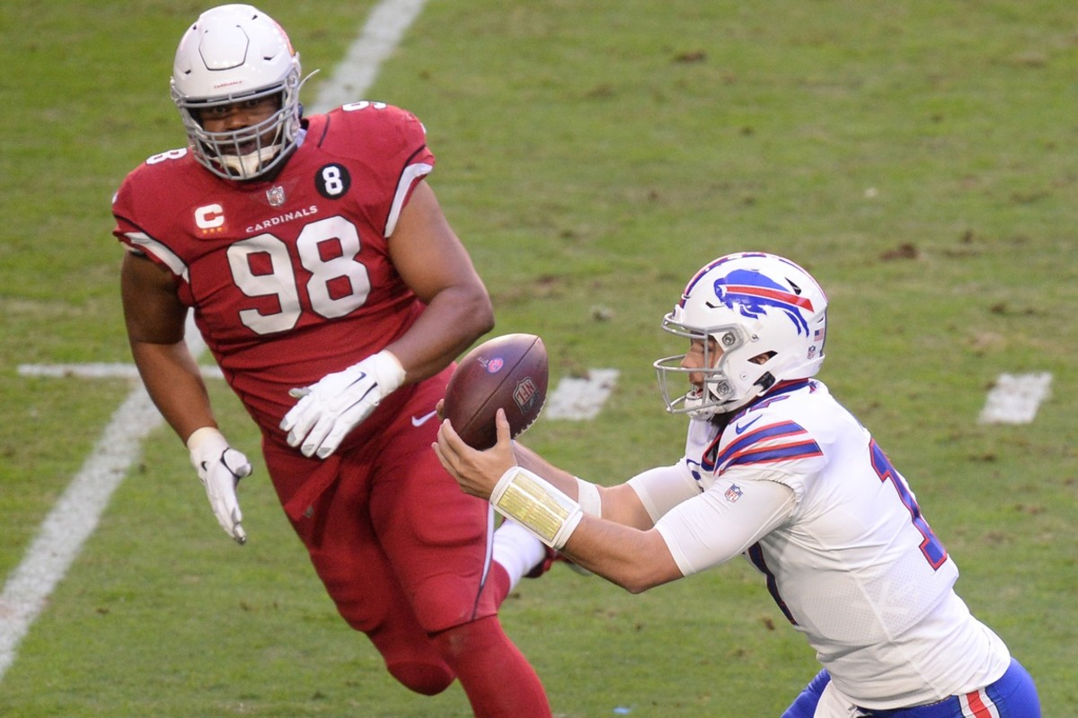Buffalo Bills quarterback Josh Allen (17) catches a pass in front of Arizona Cardinals defensive tackle Corey Peters (98) and scores a touchdown against the Arizona Cardinals during the first half at State Farm Stadium.