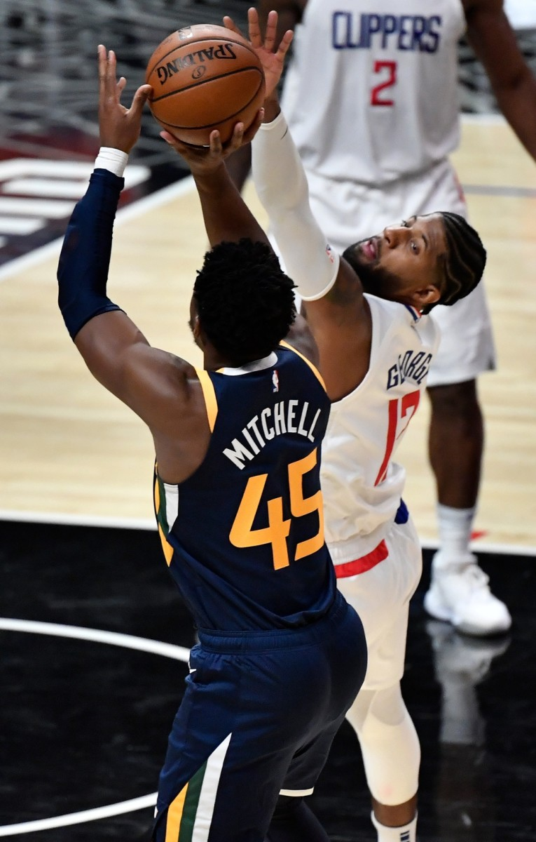 Donovan Mitchell (45) scores over Paul George (13) and the Los Angeles Clippers