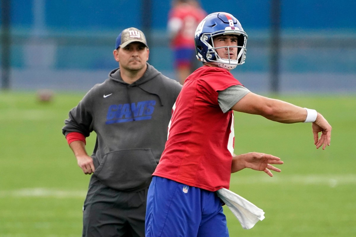 New York Giants quarterback Daniel Jones (8) throws the ball as head coach Joe Judge looks on during OTA practice at the Quest Diagnostics Training Center on Friday, June 4, 2021, in East Rutherford.