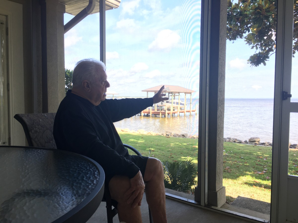 Pete Jenkins, a longtime SEC defensive line coach, gestures toward the bay from his home near the 30A area.