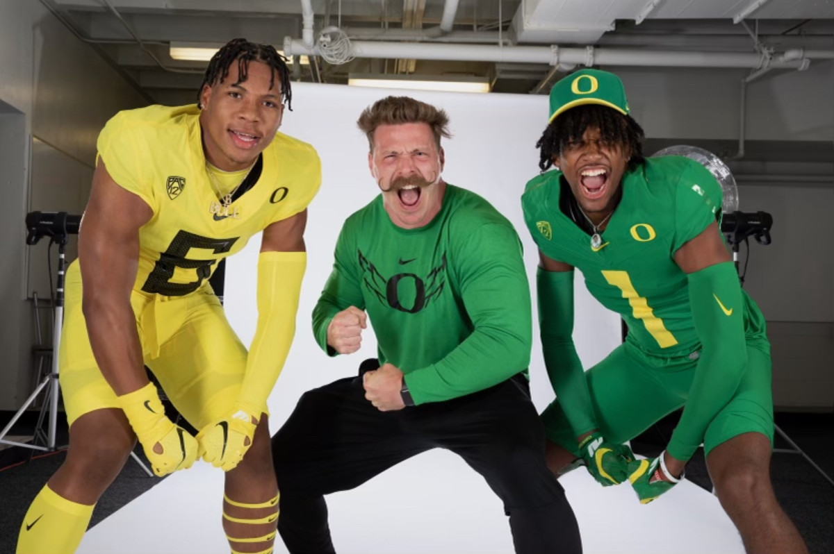 Aaron Feld flexes during a photo shoot with Oregon WR commit Stephon Johnson Jr. (1) and Oregon LB Target TJ Dudley (6).