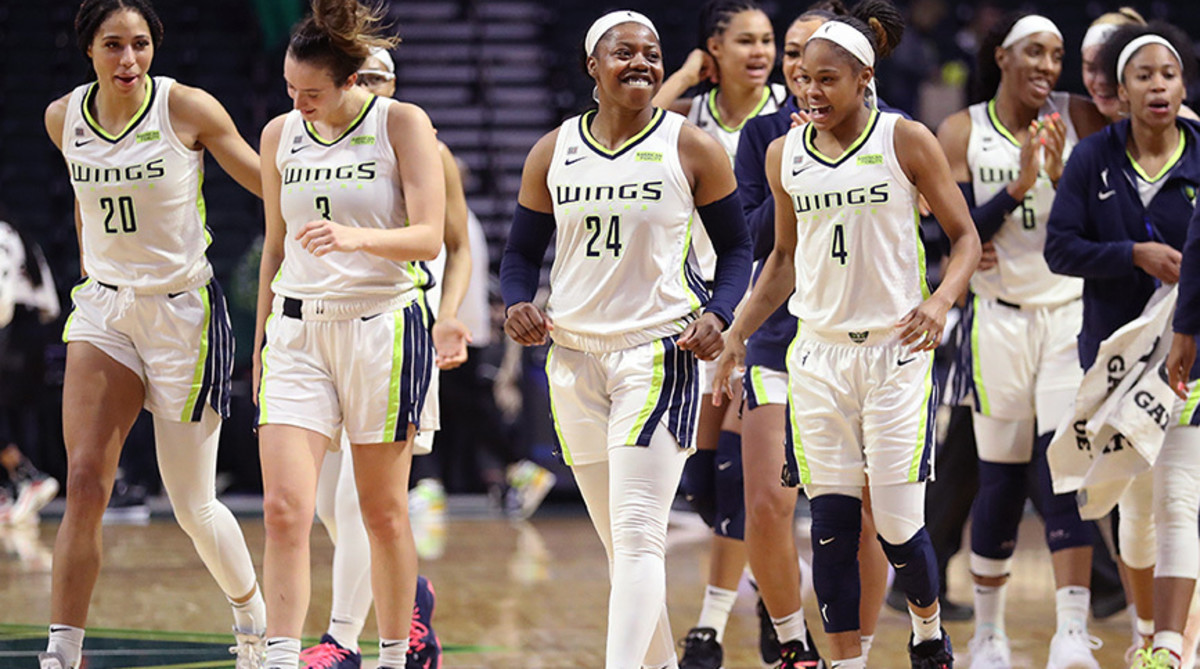 Arike Ogunbowale and the Dallas Wings smile on the court