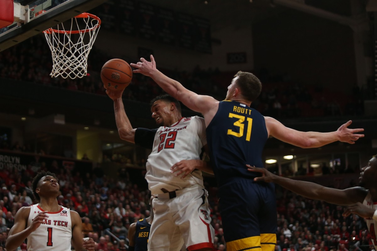 West Virginia Mountaineers forward Logan Routt (31) fouls Texas Tech Red Raiders forward TJ Holyfield (22) in the second half at United Supermarkets Arena.