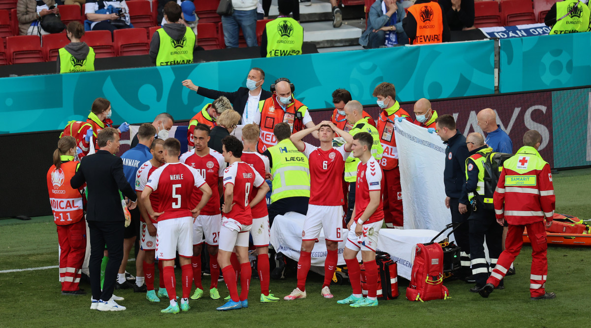 Christian Eriksen is surrounded by his Denmark teammates after he collapses on the field.